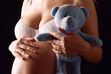 Closeup of a pregnant woman holding a toy, closeup