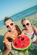 Happy summer - girls eating watermelon on the beach