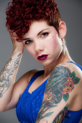 Beautiful young tattooed female in blue top