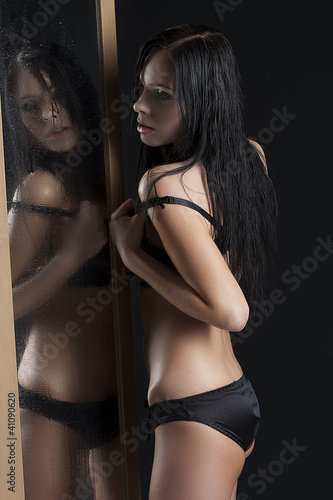 sexy woman next to a wet mirror