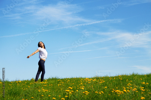 smiling young girl dancing against blue sky