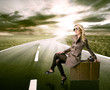 Beautiful blond woman waiting on road, concept of travel