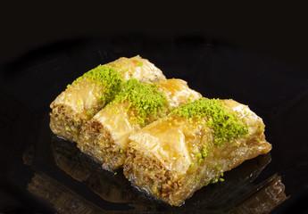 golden baklava dessert isolated on black background