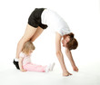 Young woman doing sport exercises with her little daughter