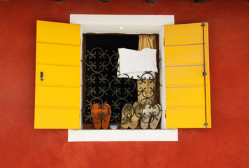 Yellow window on red wall, shoes  on the windowsill