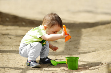 little child playing in sandbox