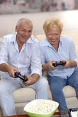 Pareja de señores jugando vídeo juego en casa.