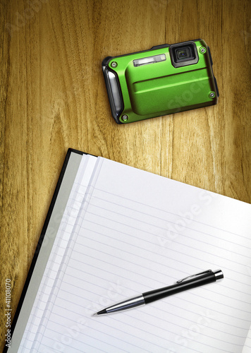 notepad and camera on desk