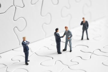 Business figures shaking hands on a puzzle