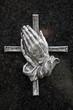 Betende Hände vor Kreuz auf dunklem Hintergrund