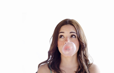 Cute young girl making a bubble with gum