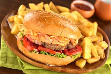 Hamburger mit Pommes auf rustikalem Holzteller