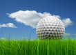 Conceptual golf ball in grass over a blue sky