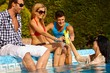 Young friends by swimming pool smiling