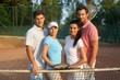 Young couples on tennis court smiling