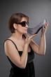 junge Frau mit Sonnenbrille küsst Schuh