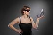 junge Frau mit Sonnenbrille präsentiert Schuh