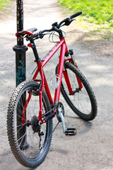 Red Bike standing near the pillar on the bike trail