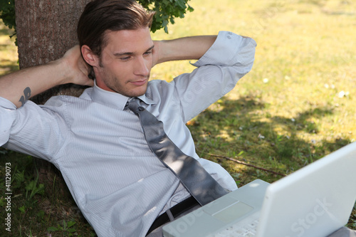 Young man relaxing in the grass with laptop
