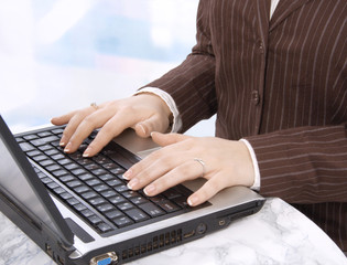 Hands of business person on notebook keyboard