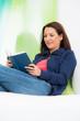junge frau liegt bequem auf der couch und liest ein buch