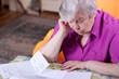 Seniorin liest in Papieren und wirkt angestrengt