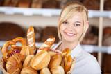 lächelnde bäckereiverkäuferin mit backwaren