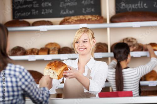 kundin kauft brot in der bäckerei - 41134608