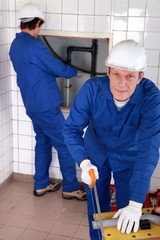 Two male plumber working together