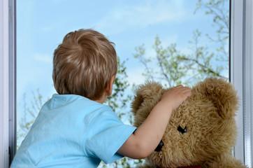 Junge mit Teddy am Fenster