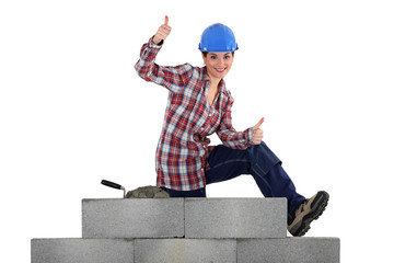 female mason sitting on a wall making thumbs up sign
