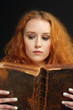 Young woman reading an old bible