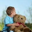 Junge mit Teddy im Garten