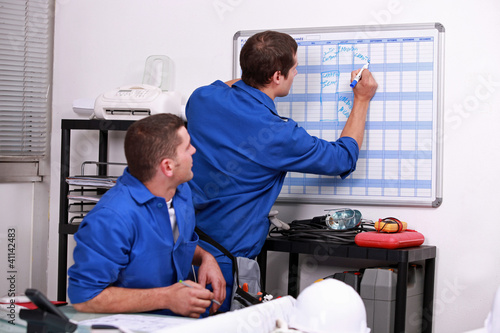 Manual workers writing on a calendar