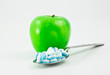 green apple and spoon full of pills