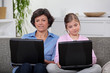 Mother and daughter each with their own laptop