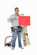 Carpenter holding red panel