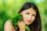 woman with bare shoulders holding bunch of parsley