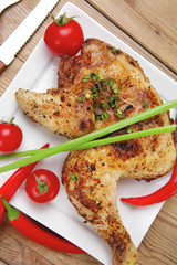 chicken quarters garnished with red hot peppers