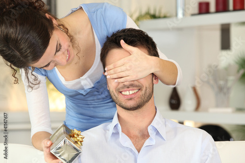 Young woman offering surprise-gift