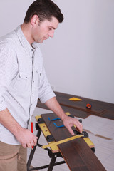 Man measuring plank of wood