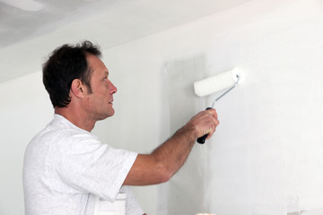 Man repainting room white
