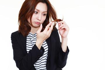 枝毛を心配する女性