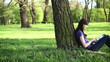Female student with tablet computer in the park, dolly shot