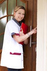 Altenpflegerin klingelt an der Tür für einen Hausbesuch ihrer