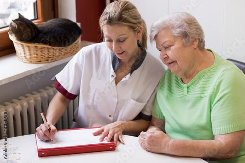 Altenpflegerin beim Hausbesuch einer Patientin