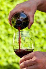 Draußen ein Weinglas mit Rotwein einschenken