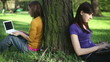 Young female students with with laptop in the park, dolly shot
