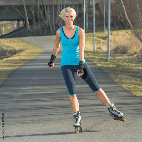 Woman roller skating in park smiling summer