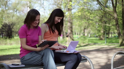 Happy female students with tablet and laptop in the park